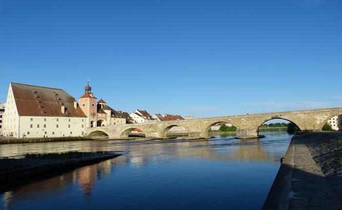 Die Steinerne Brücke in Regensburg ist eines der best erhaltensen Kulturdenkmäler Deutschlands. Auf dem Bild ist die Siluette der Stadt Regensburg mit ihren mittelalterlichen Türmen und der Steinernen Brücke im Vordergrund zu sehen.